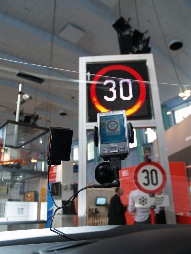Das Signalbild eines Wechselverkehrszeichens wird mittels Infrarot-Technik auf den PDA ins Fahrzeug übertragen und gibt so ständige Orientierung z.B. über Geschwindigkeitsbeschränkungen auf Straßenabschnitten. Das Cockpit im Bild wurde von MAGNA zur Verfügung gestellt, die C2X-Technologie kommt aus dem Hause EFKON, das Wechselverkehrszeichen von SWARCO.