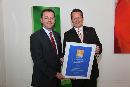 """V.l.n.r.: Umweltminister DI Nikolaus Berlakovich übergibt Hoval Österreich Geschäftsführer Ing. Christian Hofer die Urkunde zum """"GreenBuilding Award""""."""