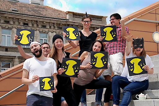 Eine Gruppe motivierter Menschen hält Schilder mit dem Logo der Europäischen Theaternacht in Händen.
