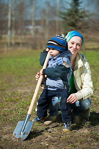 young woman and boy sits with spade in garden