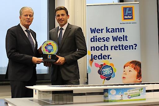 Sprecher der Geschäftsleitung und Hofer-Generaldirektor Günther Helm übergibt Wirtschafts- und Energieminister Reinhold Mitterlehner die umfassende Klimaschutzpolitik von Hofer.