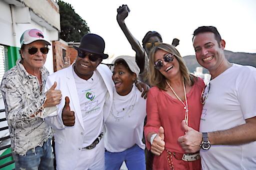 """v.l.n.r. Regisseur UIli Lommel, Tito Jackson (Sänger und Mitglied der legendären """"Jackson 5""""), die brasilianische Sängerin Mart'nalia und Dr. Christian & Christiane Hirmer (Unternehmer und Bauherren des campo bahia, Deutsches Teamhotel bei der FIFA WM 2014) an der Michael Jackson Statue in Santa Marta/ Rio de Janeiro beim Videodreh zu """"Winning by Giving"""". Der Song ist Titos Antwort auf Michaels """"They don 't care about us"""" und Hymne zum neuen News- und Charity-Portal mygoodplanet.com, gegründet von Dr. Christian und Christiane Hirmer und Ulli Lommel."""
