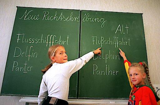 Zwei Schülerinnen, Katrin (l) und Steffi, deuten an der Tafel einer Berliner Schule auf die alte Schreibweise von Wörtern, die von der Rechtschreibreform betroffen sind (Foto vom 18.09.1997). Foto: Jens Kalaene dpa | Verwendung weltweit
