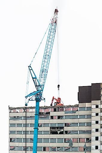 """Der sogenannte """"fliegende Bagger"""" trägt Stockwerk für Stockwerk das ehemalige Zollamt ab. Ab 2017 entsteht an diesem Standort das Hochhaus-Ensemble TrIIIple, ein Projekt der ARE DEVELOPMENT und SORAVIA GROUP."""