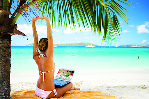 woman with her arms raised working on laptop at a tropical beach in the Caribbeanview images from the same series: