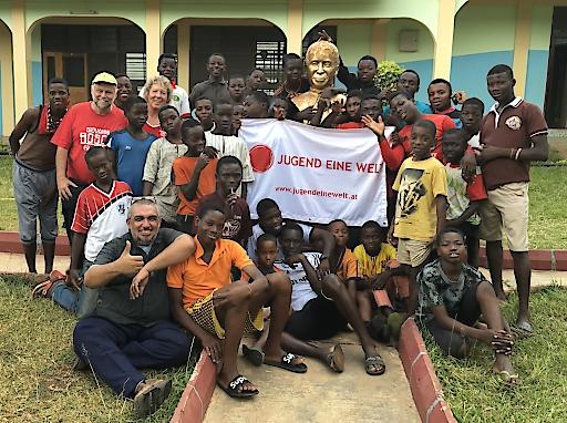 Jugend Eine Welt Vorsitzende Monika Mlinar mit ehemaligen Straßenkindern und Projektpartnern vor Don Bosco Statue in Ghana