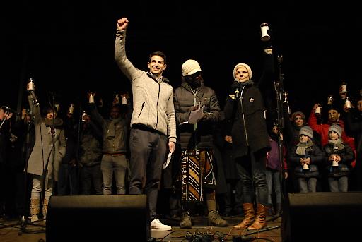 Die Bewohner George Vardayan und Baba Moussa heben gemeinsam mit Ariane Baron, Pressesprecherin des Flüchtlingsprojekts Ute Bock ihre Kerzen als Symbol für die Flamme, die in uns allen Weiterbrennen soll.