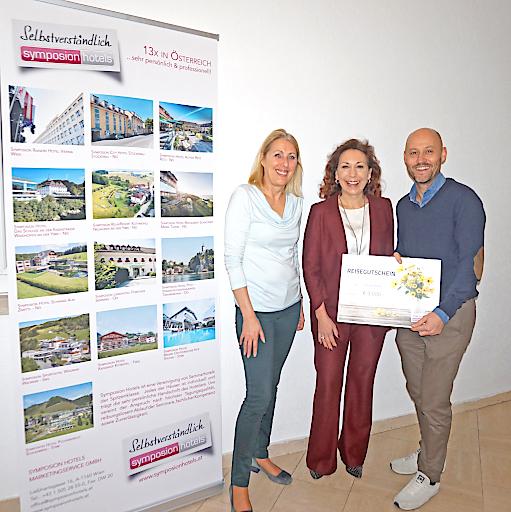 Gewinnübergabe an die Gewinnerin der Umfrage: Andrea Kernreiter, CEO Symposion Hotels; Claudia Böhm, Reisegutscheingewinnerin; Andreas Kernreiter, CEO Symposion Hotels (v.l.n.r)