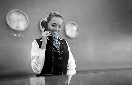 Beautiful woman working at the front desk of a hotel talking on the phone