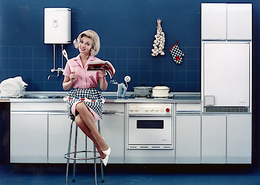 Köchin in Einbauküche der 1960er Jahre