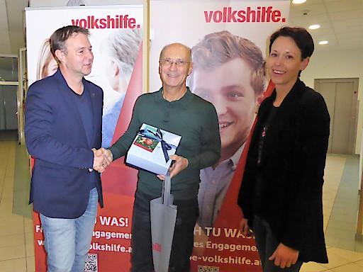 In Vertretung für alle freiwilligen Helferinnen und Helfer übernahm Gerhard Furtenbacher (mi) im Hort Traiskirchen, wo er regelmäßig hilft, ein Geschenk von Bgm. Andreas Babler (li) und Freiwilligen-Managerin Bettina Lanzenberger (re)