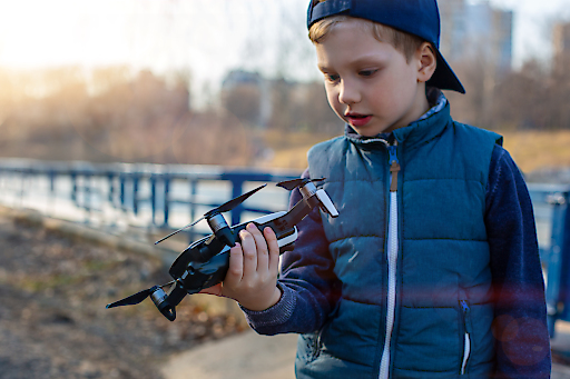 Boy manages quadrocopter, and plays with his drone in the park. Copter and boy
