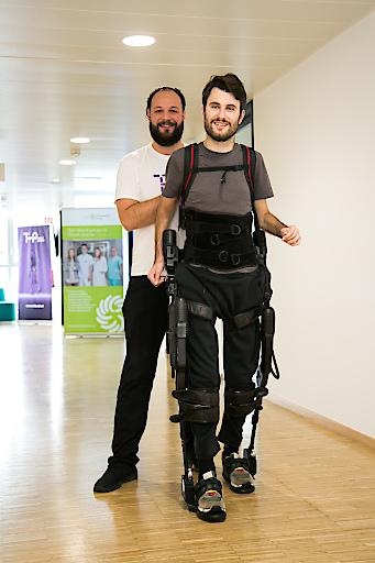 Im Bild v.l.n.r.: Therapieteilnehmer Maximilian Pölzl im Exoskelett und Physiotherapeut Dennis Veit, Mitinitiator von tech2people