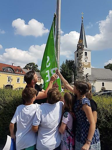 """Traiskirchen ruft als 1. österreichische Stadt den """"Climate Emergency"""" – den Klimanotstand aus. Bgm. Andreas Babler hisst gemeinsam mit Traiskirchner SchülerInnen eine Fahne als Symbol der Resolution."""