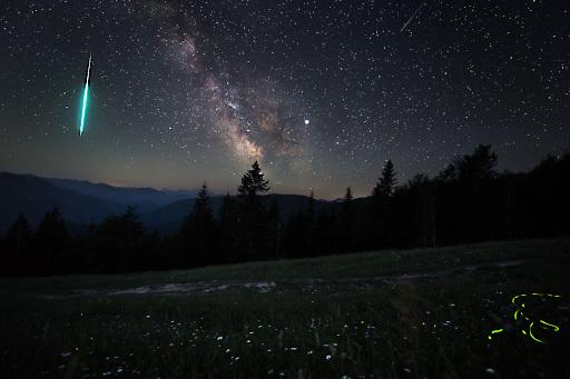 Ein Bolide (besonders helle Sternschnuppe) mit Milchstraße und Glühwürmchen (grüne Leuchtspur) im Juni 2019. Aufgenommen auf der Hohen Dirn im Nationalpark Kalkalpen, einer jener Regionen in denen man noch eine naturnahe Nacht erleben kann.