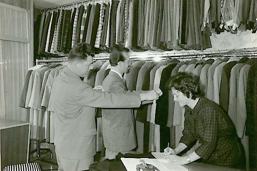 Beratungssituation aus den 1960er Jahren. Schneidermeister Erhard Kutsam und seine Frau Rosa beraten einen Kunden.