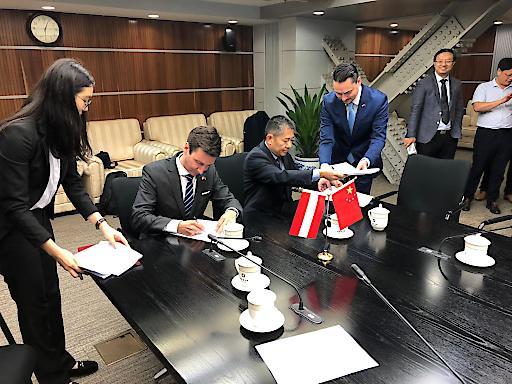 Florian Frauscher, Sektionschef im Bundesministerium für Digitalisierung und Wirtschaftsstandort und Zhai Qian, Vertreter des chinesischen Handelsministeriums, unterzeichnen das Protokoll zur 27. Tagung der Gemischten Wirtschaftskommission Österreich-China.