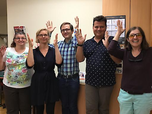 Der Vorstand des Forums für Usher Syndrom und Taubblindheit. Die Vorstandsmitglieder applaudieren fröhlich in Österreichischer Gebärdensprache.