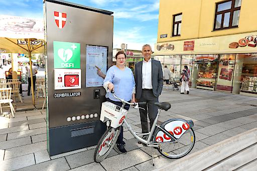 Gewista CEO Franz Solta mit der Gewista CSR-Verantwortlichen Andrea Nowak-Mann vor einem digitalen City Light der Gewista mit eingebautem Laien-Defibrillator und einem Citybike der Gewista.