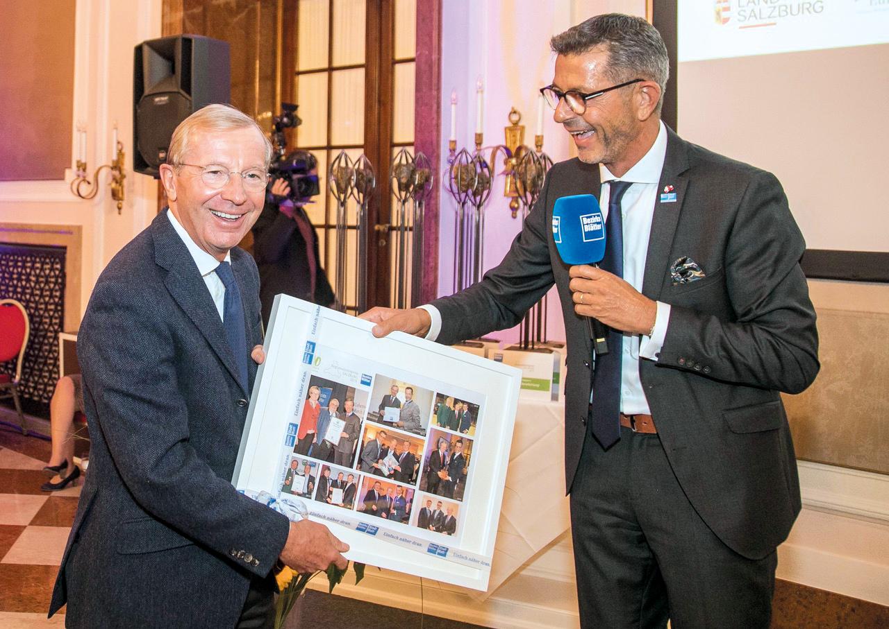 Landeshauptmann Wilfried Haslauer freut sich über seine Fotocollage die ihm Bezirksblätter-Geschäftsführer Michael Kretz überreichte.