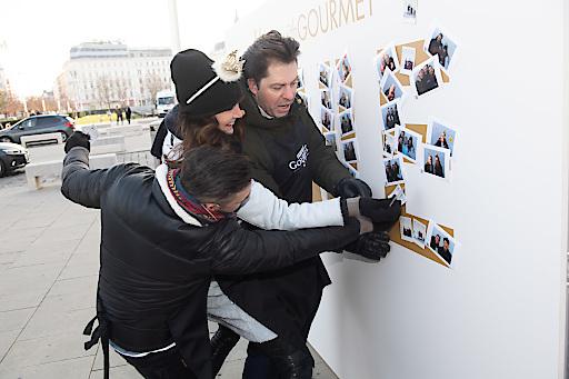 Andi Moravec, Maggie Entenfellner und Daniel Serafin bekleben die GOURMET Smile-Wall