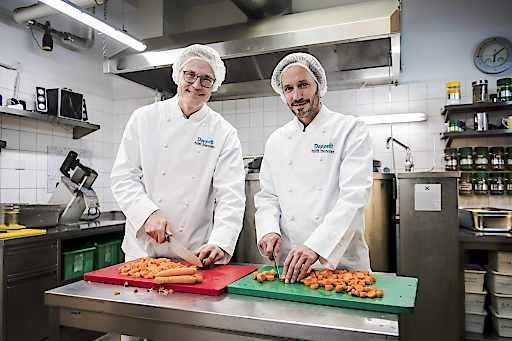 Jan Trionow (Drei) und Klaus Schwertner (Caritas Wien) beim Gemüseschneiden in der Canisibus-Küche.