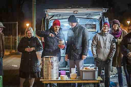 Caritas Wien-Generalsekretär Klaus Schwertner und Drei CEO Jan Trionow (2.u.3.v.l.) gemeinsam mit Canisibus-Freiwilligen beim Austeilen warmer Mahlzeiten in der Kälte.