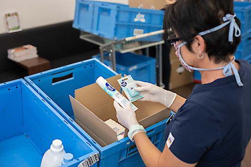 Auch beim Verpacken der Online-Bestellungen tragen die dm Mitarbeiter Mund-Nasen-Masken und Handschuhe.
