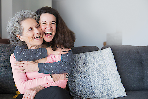 Portrait of happy mid adult woman embracing her senior mother. Mother and daughter at home, family scene. Family relationships concept