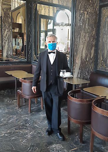 Immer ein Lächeln für die Gäste – auch unter der Maske. Andreas Schwabl, Oberkellner im Café Schwarzenberg, freut sich darauf, bald wieder die Gäste begrüßen zu dürfen.