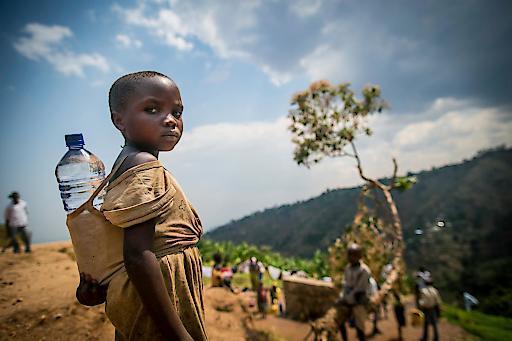 Ein Kind in Bujumbura Rural benutzt eine Wasserflasche, um sich Trinkwasser nach Hause zu bringen.