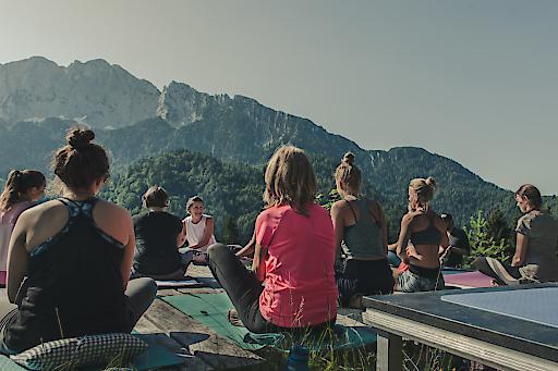Morgendliche Yogasession am Brentenjoch mit Panoramablick auf das Kaisergebirge.