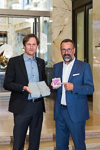 Sebastian Spaun (links) und Rudolf Zrost (rechts) zeigen anhand eines Probewürfels die Carbonatisierung von Beton.