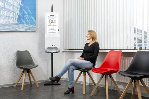 Frau schaut sich Corona-Kampagne auf IDS-Sanitizer mit eingebautem Display in Wartezimmer an.