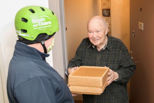 Karl Fellinger, Zusteller des Samariterbund Wiens (li.) bringt Herrn Hellmut Müksch das Essen auf Rädern.