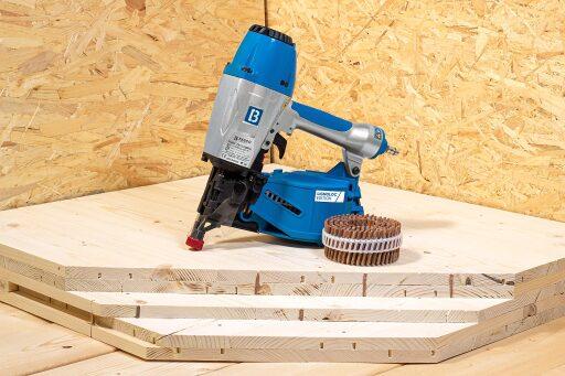 Hand-Druckluftnagler F44AC CN15-PS60A LIGNOLOC® mit Holznagel-Coil auf mit LIGNOLOC® Holznägeln gefertigtem Massivholzaufbau-Muster.