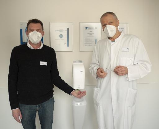 Hygienefachkraft Uwe Riedesel und der hygienebeauftragte Arzt Dr. med. Michael Kaiser begutachten die neuen Händedesinfektionsmittelspender im Brüderkrankenhaus St. Josef in Paderborn (auf dem Bild von links)
