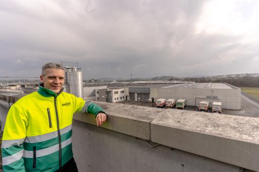 Braumeister Christian Huber blickt hinüber auf die neue Photovoltaikanlage am Dach der Logistikhalle in der Brauerei Wieselburg.