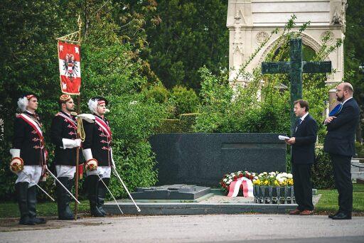 MKV Vorsitzender Walter Gröblinger, Couleur Philipp Jauernik und drei junge Männer an der Standarte des MKV stehen vor dem Ehrengrab von Leopold Figl am Zentralfriedhof