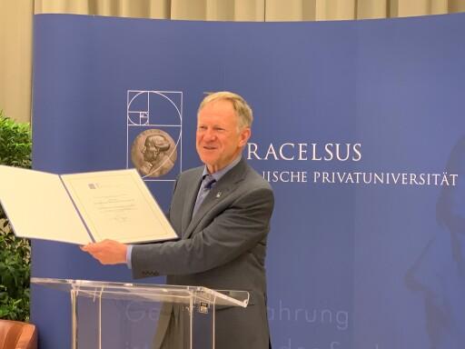 Rektor Prof. Wolfgang Sperl mit der Urkunde