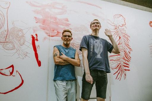 TOMAK, Leiter des Kunstprojektes Aktion 11 und Christian Öllinger, Künstler, Die Kunstwerkstatt │Diakoniewerk vor dem Fries im Aktionsraum LINkZ. (v.l.n.r.)