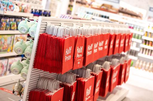 Rote Einkaufstaschen aus Papier mit HalfPrice-Logo.