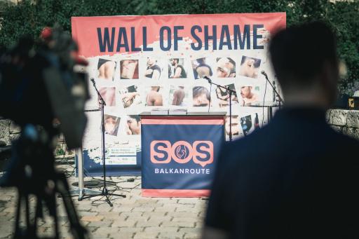 """Bei der Übergabe von Beweisen an österreichische NR-Abgeordneten stellten AktivistInnen von SOS Balkanroute eine """"Wand der Schande"""" vor dem Innenministerium auf. Im Mittelpunkt stehen die Verletzungen durch illegale Pushbacks."""