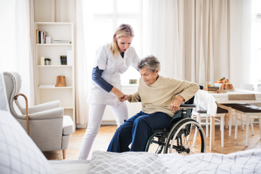 A young health visitor helping a senior woman to stand up from a wheelchair at home.