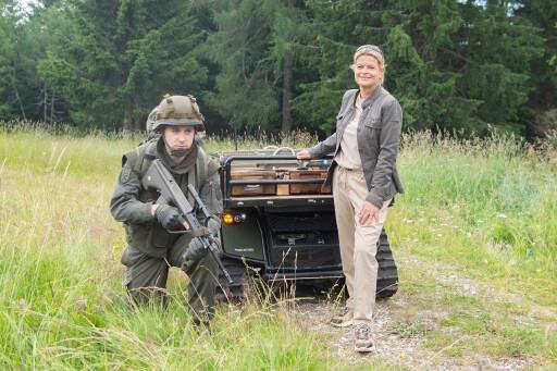 Verteidigungsministerin Klaudia Tanner mit einem Forschungsroboter, der Soldaten beim Transport unterstützen könnte.