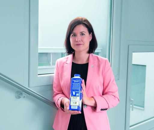 Veronika Breyer, Marketingleiterin der NÖM AG mit der Packung auf der die Notrufnummer zu sehen ist. ©NÖM AG